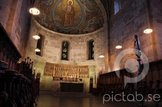 Lunds domkyrka interiör  Lunds domkyrka är en kyrkobyggnad i parken Lundagård i centrala Lund. Den är domkyrka i Lunds stift och församlingskyrka för Lunds domkyrkoförsamling. Lunds domkyrka kom till på 1100-talet efter att Lund hade blivit säte för Nordens ärkebiskop. Kyrkan byggdes av sandsten i romansk stil av stenhuggare från Rhen och Italien. Lunds domkyrka anses vara Nordens främsta efterföljare till kejsardomen i Speyer.  Det är svårt att datera domkyrkans egentliga grundläggande. I Knut den heliges gåvobrev, daterat till 21 maj 1085, talas om en domkyrka byggd under 1080-talet. Mycket tyder dock på att detta inte rör sig om samma domkyrka och att den nuvarande domkyrkan började byggas under tidigt 1100-tal när Lund blivit säte för ärkebiskopen.